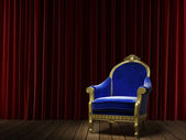 Blue classic armchair on red curtain — Stock Photo