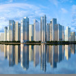 Skyscraper skyline reflected on water - Stock Photo