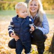 Cute kid and pretty mom outdoors at fall. — Stock Photo