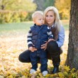 Attractive young mother with her son in the park. — Stock Photo