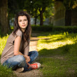 Portrait of beautiful young brunette sitting relaxed in the park — Stock Photo #8183635