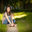 Portrait of beautiful young brunette sitting relaxed in the park — Stock Photo