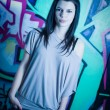 Urban portait of a beautiful young brunette girl with graffiti b — Stock Photo