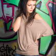 Urban portait of a beautiful young brunette girl with graffiti b — Stok fotoğraf