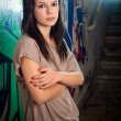 Stock Photo: Urban portait of a beautiful young brunette girl with graffiti b