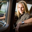 Beautiful young blond girl in a black vintage car. — Stock Photo