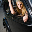 Royalty-Free Stock Photo: Beautiful young blond girl in a black vintage car.