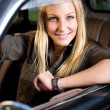 Beautiful young blond girl in a vintage car. — Stock Photo