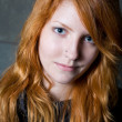 Disillusioned smile - moody portrait of beautiful young redhead — Stock Photo