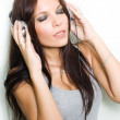 Hot young brunette enyjoying music. — Stock Photo