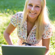 Beautiful young blonde using laptop in nature. - Foto de Stock