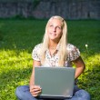 Gorgeous young blond having fun with laptop outdoors — Stock Photo