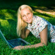 Beautiful young blond using laptop outdoors in nature. — Stock Photo