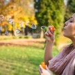 Blowing bubbles into the wind. — Stock Photo