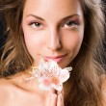 Beauty shot of gorgeous brunette holding flower. — Stock Photo #8187960