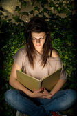 The magic of books. Beautiful yopung brunette immersed in readin — Stock Photo
