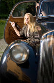 Beautiful young blond girl posing with a black vintage car — Stock Photo
