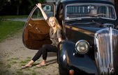Beautiful young blond girl posing with a black vintage car — Foto Stock
