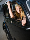 Vacker ung blond flicka i en svart vintage bil. — Stockfoto