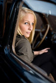Portrait of a beautiful young blond in a vintage car. — Stock Photo