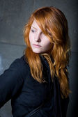 Moody portrait of a beautiful young redhead girl. — Photo