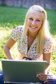 Beautiful young blonde using laptop in nature. — Stock Photo