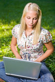 Cute young blond having fun with laptop outdoors. — Stock Photo