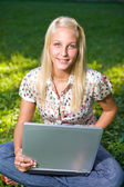 Pretty young blond girl with laptop in the park. — Stock Photo