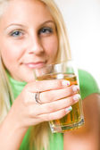 Beautiful young blonde girl holding a glass of apple juice, focu — Photo