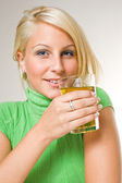 Beautiful young blonde girl holding a glass of apple juice, focu — Stok fotoğraf