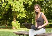 Cute young teen using latop outdoors. — Stock Photo