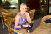 Beautiful young blond having fun with laptop. — Stock Photo