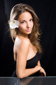 Beauty shot of gorgeous brunette with flower. — Stock Photo
