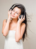 Brunette immersed in music wearing headphones. — Stock Photo