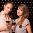 Two beautiful brunettes tasting wine. — Stock Photo