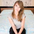 Lonely girl sitting on the bed. — Stockfoto