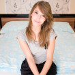 Lonely girl sitting on the bed. — Stock Photo