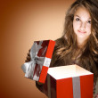 Young brunette with big red gift box. — Stock Photo