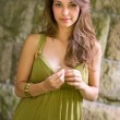Beautiful young brunette posing in green dress. — Stok fotoğraf
