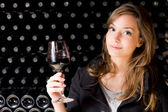 Beautiful young woman tasting wine. — Photo