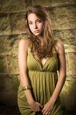Beautiful young brunette posing in green dress. — Stock Photo