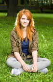 Romantic portrait of a young redhead girl sitting in the park. — Stock Photo