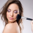 Young brunette getting makeup, with brushes. — Stock Photo #9099508