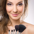 Young brunette getting makeup, with brushes. — Stock Photo #9099536