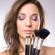 Gorgeous brunette woman with makeup tools, brushes. — Foto de Stock