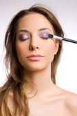 Gorgeous brunette woman with makeup tools, brushes. — Stock Photo