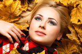 The beautiful blonde lies in autumn foliage — Stock Photo