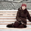 Young woman in winter park on a bench — Stock Photo