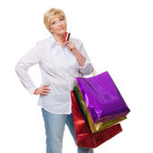The woman with a credit card and purchases pensively looks upwar — Stock Photo