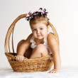 Little girl sitting in the basket — Stock Photo